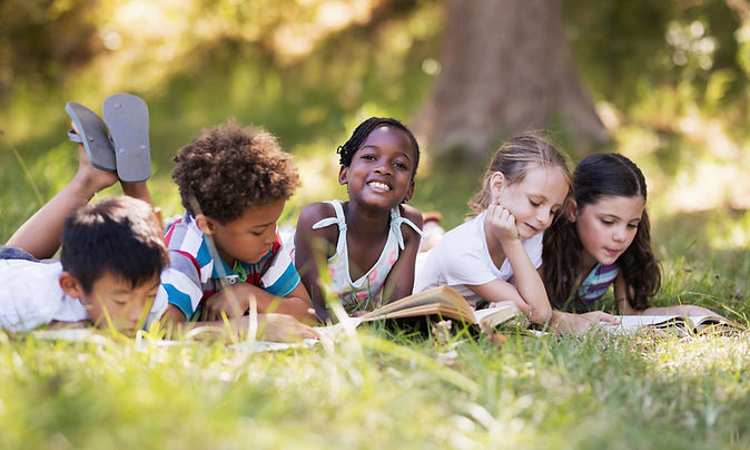 five kids of different etnicity reading outside in the grass.