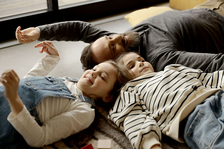 Father and daughters having family time cuddling on the floor Paisley, UK