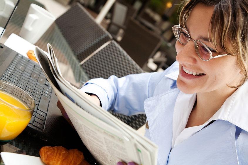 Mulher lendo o jornal da manhã