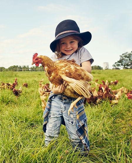 Entzückendes Kind, das Huhn hält