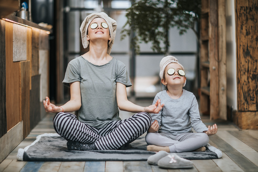 mother and daughter meditating with cucumbers on eyes