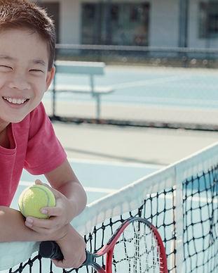 Junge auf einem Tennisplatz