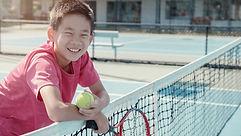テニスコートにいる少年