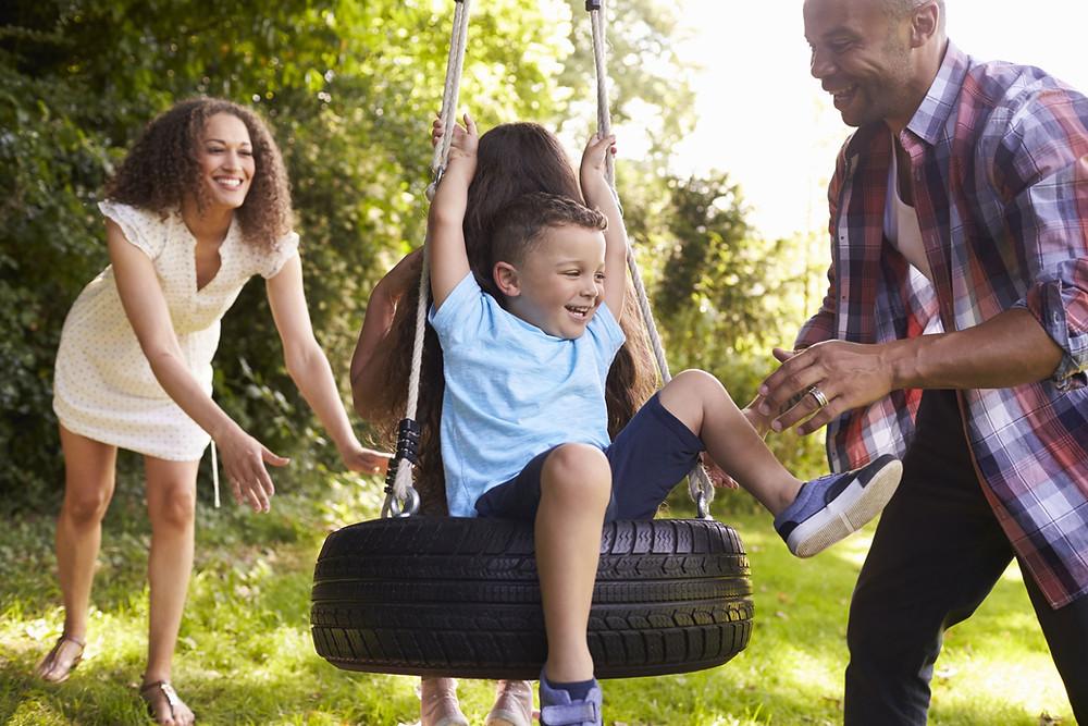 Familie auf dem Spielplatz. Die Eltern schubsen die Kinder auf einer Reifenschaukel an