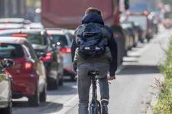 pov of cyclist riding next to cars