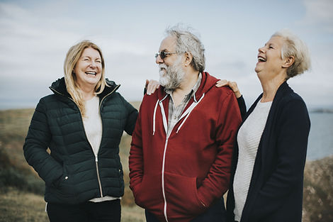 3 middle age people laughing outside