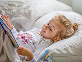 Liten jente som leser i sengen