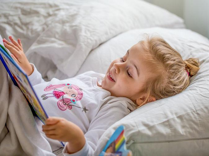 Little Girl Reading in Bed