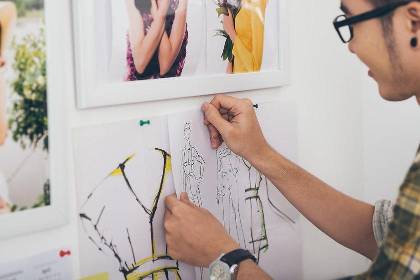 Artiste accrochant ses croquis de mode
