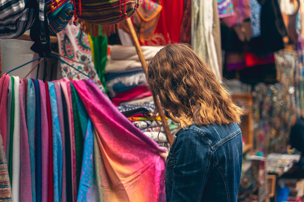 Woman looking at brightly colored clothing