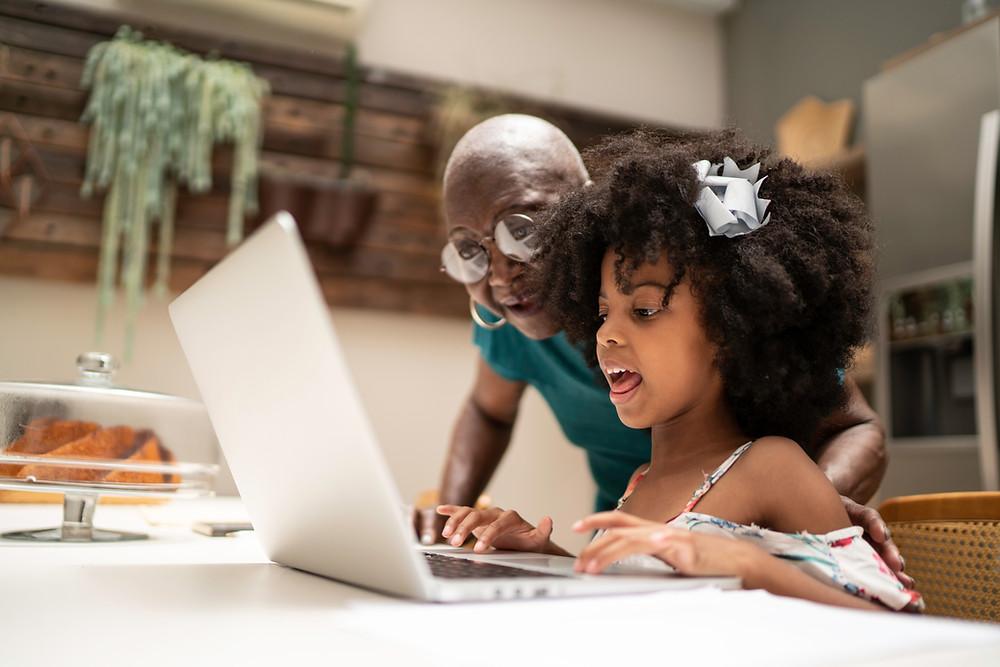 menina e avó olhando para o laptop