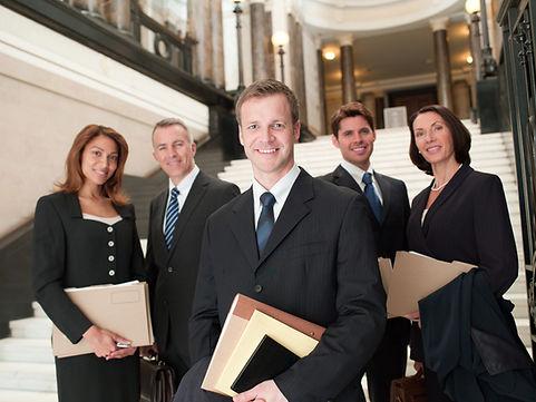 Un groupe d'avocats sourient dans le hall d'un tribunal