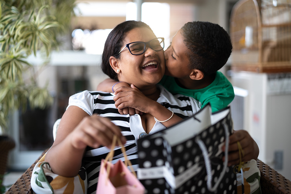 son giving mother a kiss on the cheek with gift bag on the table