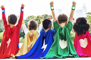 A group of children with capes raise their arms, facing away from the camera.