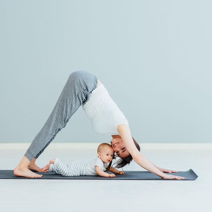 Mor som gjør yoga med baby