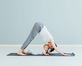 Mor som gör yoga med barnet