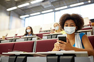 Woman, wearing face mask, browsing on cell phone in a lecture hall