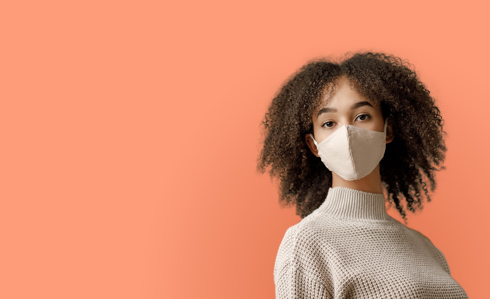 women against orange background wearing a face mask