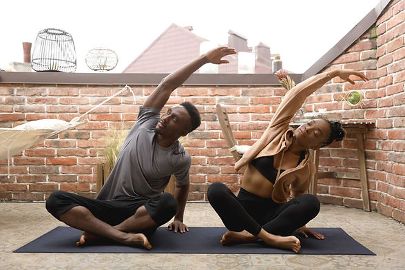 Young couple doing yoga together at home, on the deck, stretching to one side, finding calm.