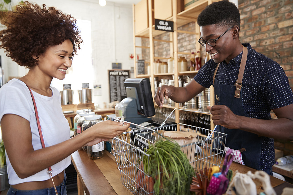 Clerk rings up customer groceries.