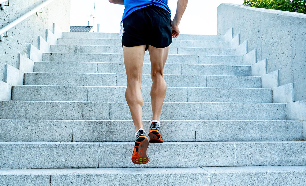 fitness male model running up stairs in athletic sneakers