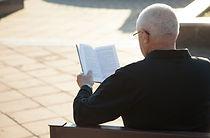 屋外で本を読んでいる男