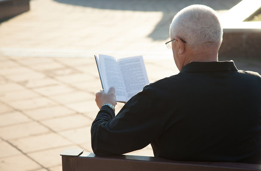 Um homem lendo um livro ao ar livre