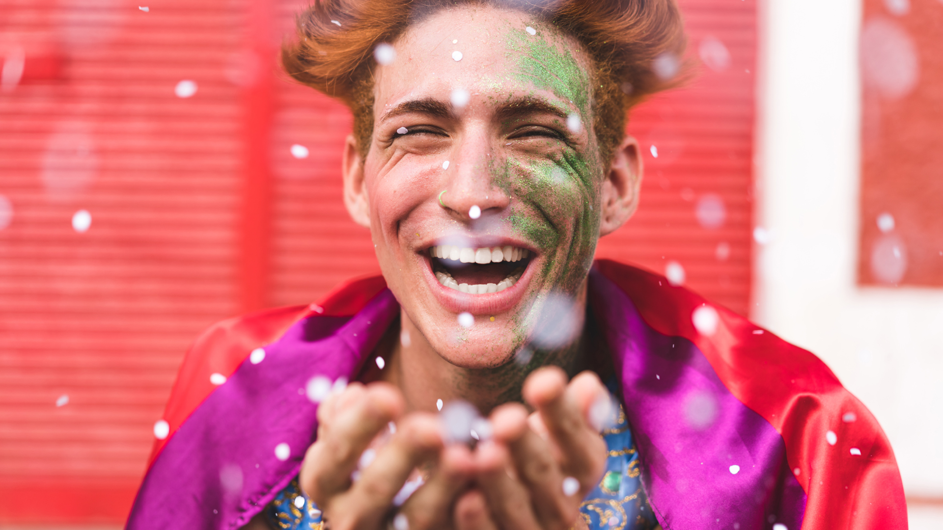 An adult with a painted face at a festival with their hands cupped catching glitter