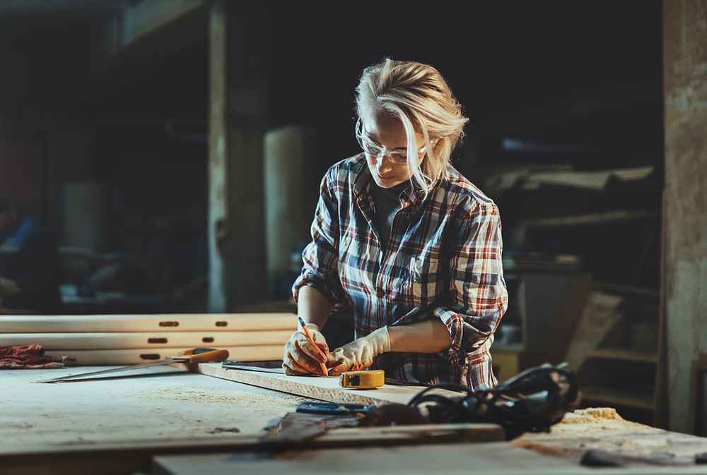Woman experiencing anxiety and getting her work done in a warehouse in a perfect fashion wearing a flannel.