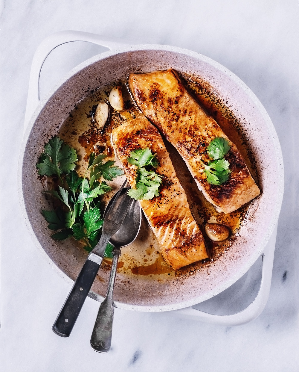 salmon in a bowl with garlic and greens