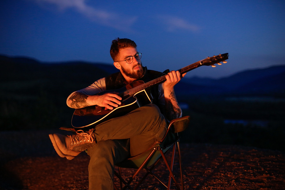A man playing a guitar by the fire