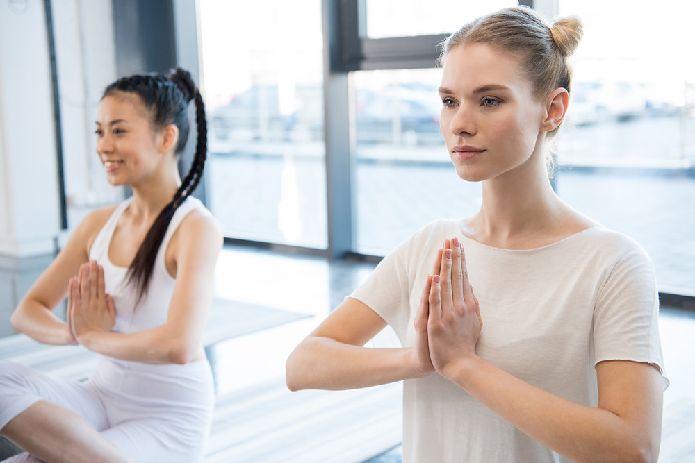An Asian and Norwegian woman enjoy social distancing while doing breathing yoga