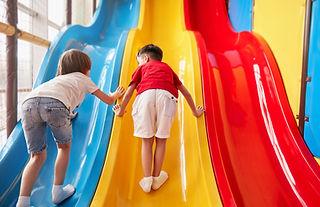 Boys Climbing Up Slide