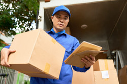 Delivery Man with parcel in front of truck