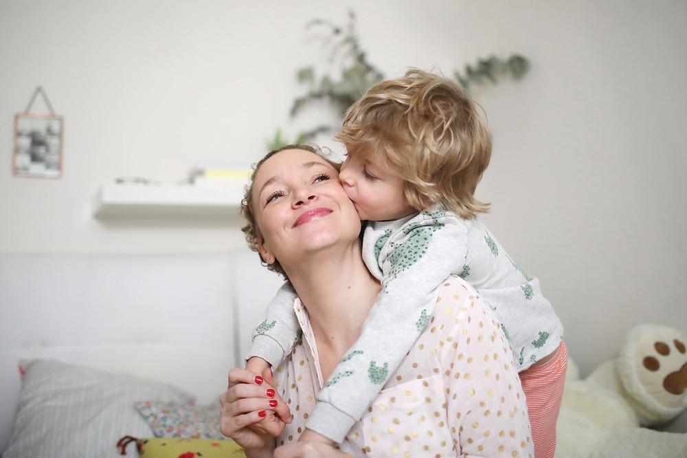 un enfant enlcae par derrière sa maman et lui donne un bisou