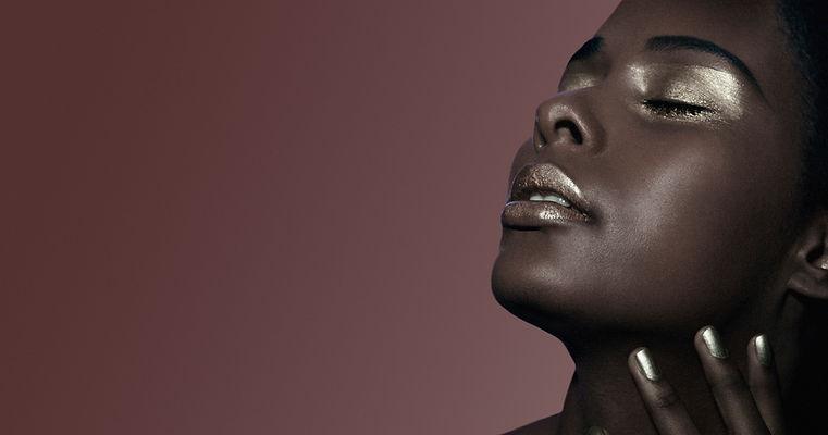 A beautiful black woman wears metallic eyeshadow and lips Makeup