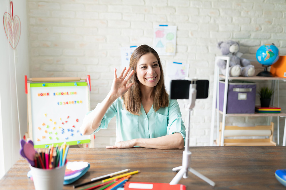 "Women sits in front of her phone waving her right hand. Behind her is a white board that reads ""Home Schooling"" and the number 1-9."