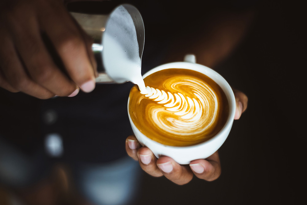Cappuccino cup with milk pouring into a design