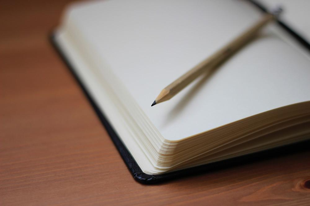 Avoin muistikirja, tyhjän sivun päällä lyijykynä.
