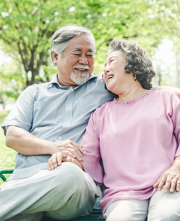 Older couple sitting on park bench smiling at each other