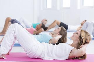 Frauen machen Pilates Übungen auf der Matte