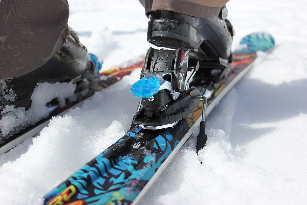 Skier stepping into skis with white snow underneath.