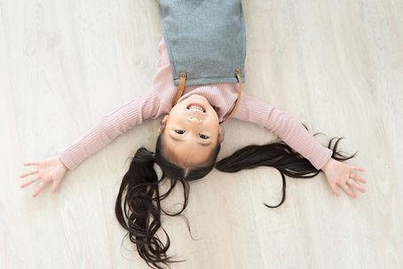 床に寝そべる少女