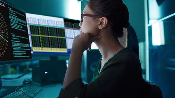 画面上のチャートを見ている女性