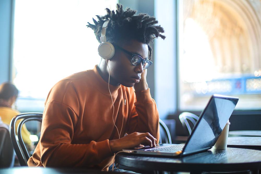 Homem em frente a um computador com fones de ouvido