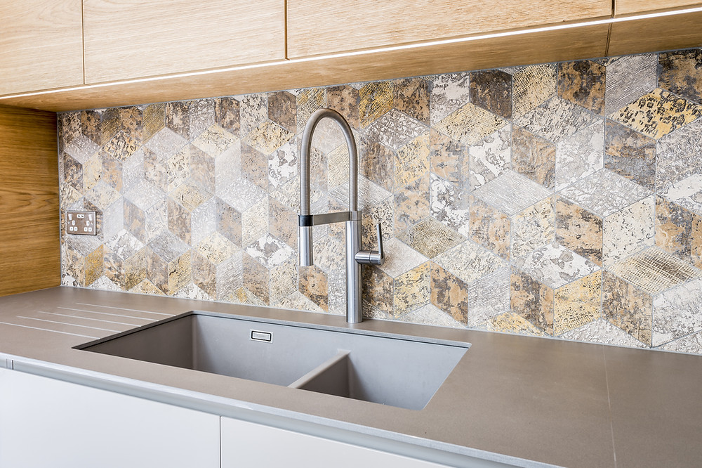 A Brown Argyle Shaped Backsplash Behind a Faucet In the Kitchen/
