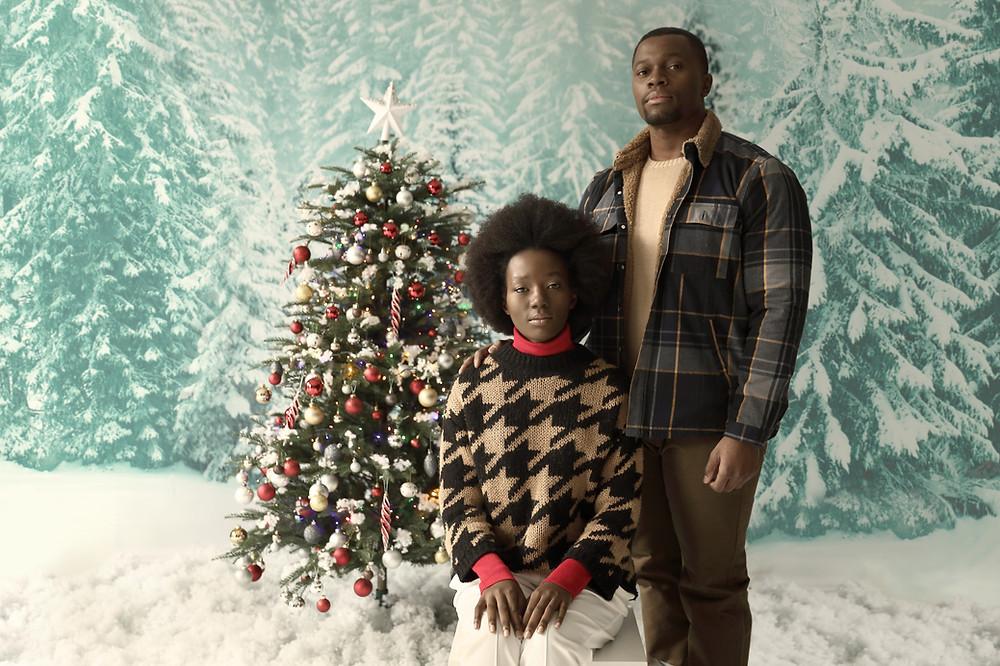 Couple d'entrepreneurs Noirs posant devant un arbre de Noël