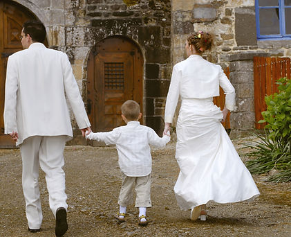 Couple de mariés tenant la main d'un enfant