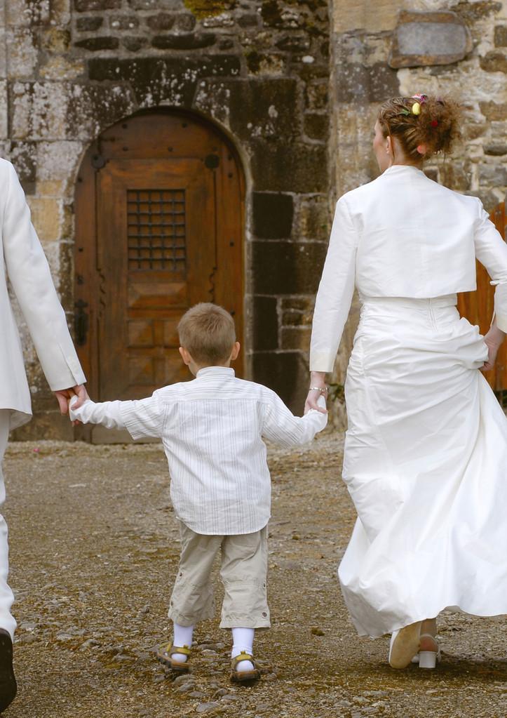 Couple de mariés tenant la main d'un enf
