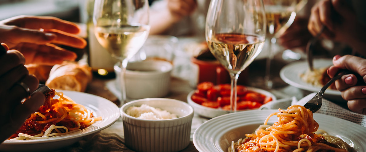 people eating spaghetti and wine